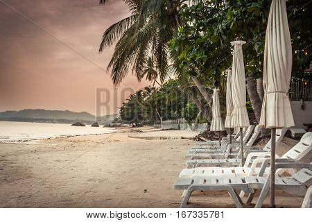 Deserted tropical beach with sunbeds and umbrellas among palm trees without people during beautiful orange sunset in hidden paradise