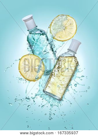Two bottles of cosmetic moisturizing lotion in the big water splash. Two lemon slices near the bottles. Turquoise gradient background