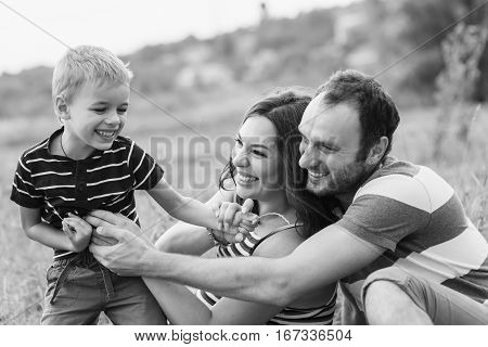 Little boy playing with his parents. Happy young family on a walk. Mother is expecting a baby. Pregnant woman, husband and their son playing outdoors. Black and white photo.