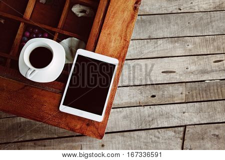 Cup of morning tea or coffee and tablet with blank screen on the wooden table over porch deck. Top view.