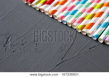 Colorful striped cocktail straws on gray background