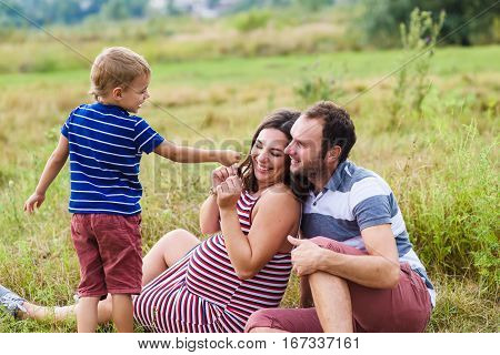 Child tickles his pregnant mother a blade of grass. Mother is expecting a baby. Pregnant woman, husband and their son playing outdoors. poster