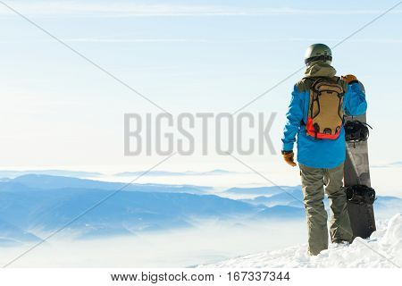 Young Snowboarder In Helmet Standing Next To Snowboard Thrusted Into Snow With Beautiful Scenery On
