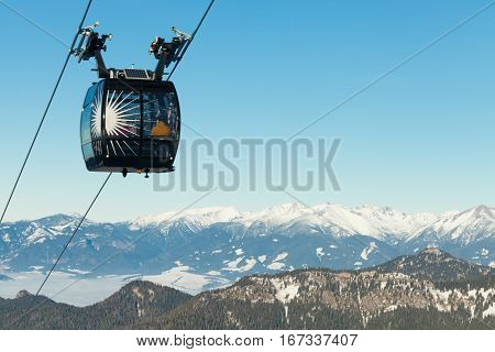 Cable car cabin going up above the clouds to the top of a mountain with a beautiful scenery on background