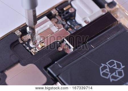 Closeup with used smartphone repair with screwdriver