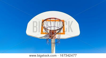 Basketball hoop and backboard--horizontal view from front and center with a sky background.