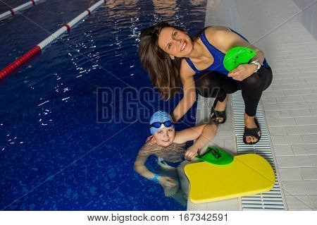 Children's swimming coach trains the boy. learning to swim at swimming pool