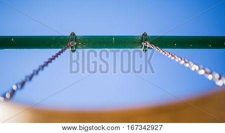 Play park kid's swing. Depth of field/horizontal view from below the swing seat.