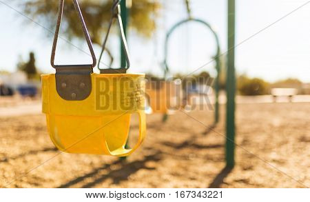 Play park toddler swings in a row. Depth of field view and close up of first swing/harness.