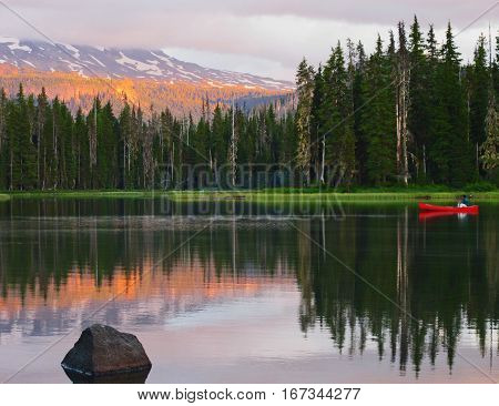 A man in a canoe at sunset with trees and the Middle Sister of Oregon's Cascade Mountains reflecting in Scott Lake on a summer day.