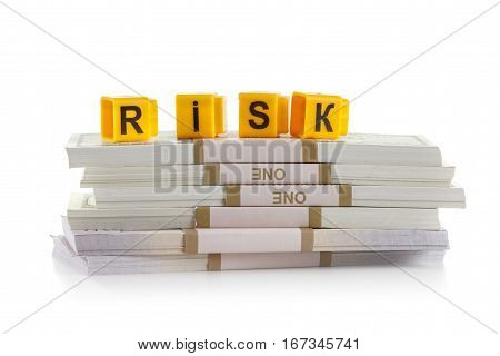 Concept investments risk word made by letter blocks. Stack of money american hundred dollar bills