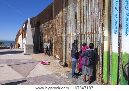 PLAYAS DE TIJUANA MEXICO - JANUARY 28 2017: Mexican families living in Tijuana visit with family members living in the United States by meeting at the border wall in Playas de Tijuana on a sunny winter Saturday morning.