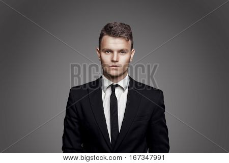 Portrait of young trendy man in black suit with tie on gray background.
