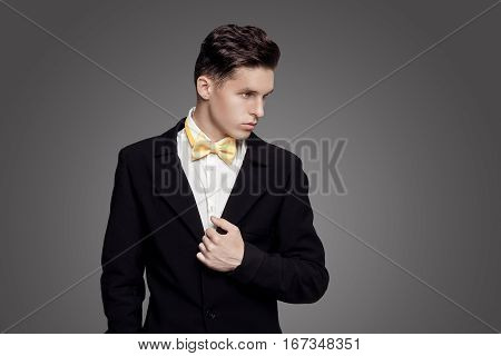 Portrait of young trendy man in black suit with yellow bow-tie on gray background.