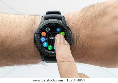 CHESTER UK - January 28 2017: Samsung Gear S3 smartwatch shown on a male wrist and operating the touch screen.