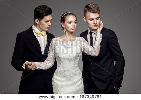 Two handsome men in suits and beautiful woman in white bridal dress. Studio, trendy, strict look.