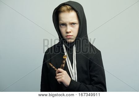 Portrait of a handsome teenage bad boy with slingshot and stylish haircut, softbox lighting studio shot.