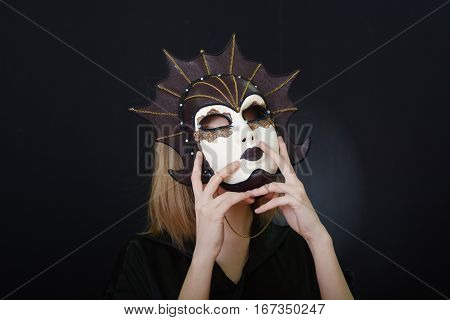 beautiful blonde girl in a theatrical mask on a dark background
