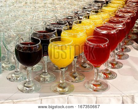 Transparent glasses with juice and soft drinks on the table with a white tablecloth