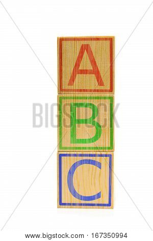 Letters A B and C imprinted on stacked brown wooden cubes on white background
