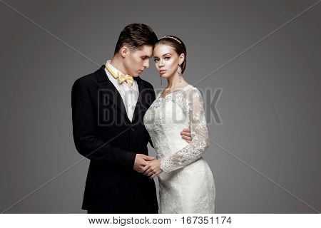 Groom in black suit and yellow bow-tie with bride in wedding dress.
