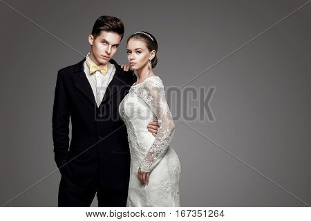 Groom in black suit and yellow bow-tie with bride in wedding dress