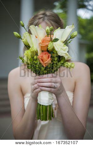A Bride hiding face behind bridal bouquet
