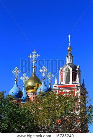 Domes of the Orthodox church on the background of blue autumn sky