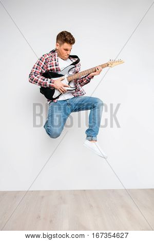 Portrait Of Trendy Rocker Guy Jumping With Electric Guitar