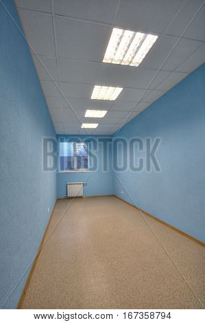 Empty office with blue walls and one window.