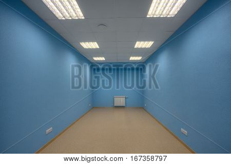 Small abandoned unfurnished office no body and no windows the walls are painted in blue.