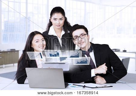 Group of three multi ethnic business team smiling at the camera with virtual financial statistic on the laptop in the office