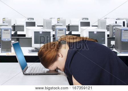 Portrait of young businesswoman looks tired and feels sleepy while resting on a laptop in the office