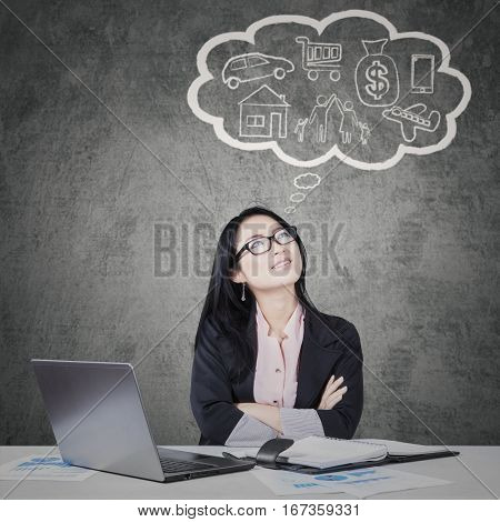 Image of thoughtful businesswoman looking at her dream on a bubble cloud while working with laptop and paperwork