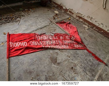 Red flag lying on the ground of a building in the ghost town Pripyat in the Chernobyl Exclusion Zone which was established after the nuclear disaster in 1986