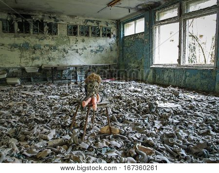 Room full of gas masks with a doll on a chair in the ghost town Pripyat in the Chernobyl Exclusion Zone which was established after the nuclear disaster in 1986
