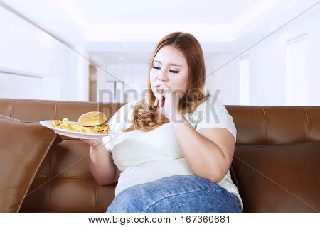 Portrait of overweight woman looks hungry and eat a junk food while sitting on the couch