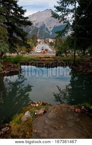 Pond in front of the road through the town of Banff in Canada with the mountain in the background.