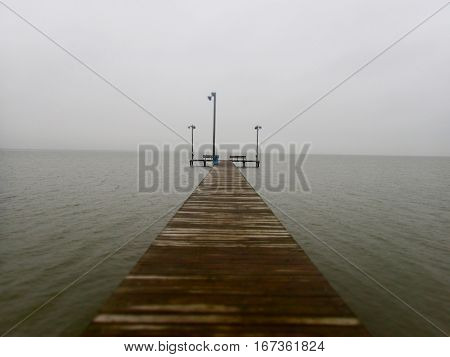 A wooden pier stretches into the ocean fog at the gulf of Mexico in Texas.
