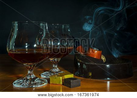 Scotch drink and tobacco pipe with smoke on black background. Two old fashioned whiskey glass and chocolate piece. Unhealthy still life or bad habits concept. Clear brandy or bourbon snifter.