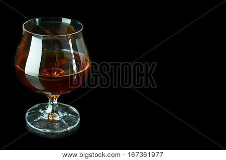 Scotch drink on black background. Old fashioned whiskey glass as loneliness symbol. Unhealthy still life or bad habits concept. Clear brandy or bourbon snifter.