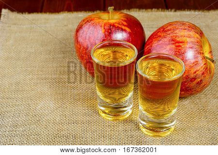 Two schnapps drinks and red apples on the rustic burlap background