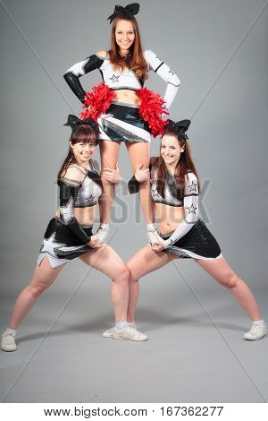 Studio shot of cheerleader team performing a thigh stand
