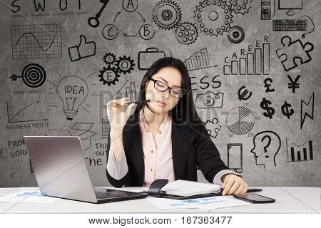 Young businesswoman is holding pen and reading document while finding solution with doodles on the blackboard
