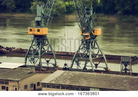Metals recycling on a river bank with freighter in a background