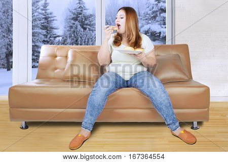 Image of obese beautiful woman eating a plate of donuts on the couch with winter background on the window