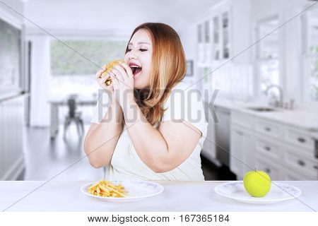 Obese beautiful woman ignores to eat apple fruit and choose to eat a junk food while sitting in the kitchen