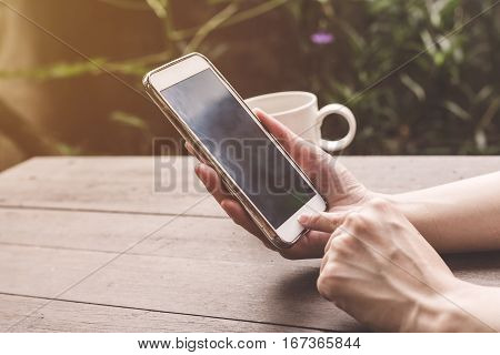Close Up Hand Woman Holding And Using Phone On Wood Table With Vintage Toned.