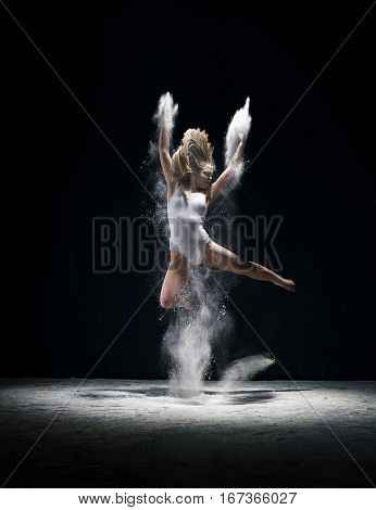 Female sexy long haired blonde in beige bodysuit dancing gracefully on black background white dust all over body studio shot
