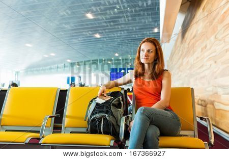 Female traveller sitting with ticket in her hands.